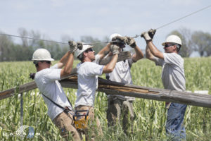 Photo of line workers repairing damage after a summer storm.