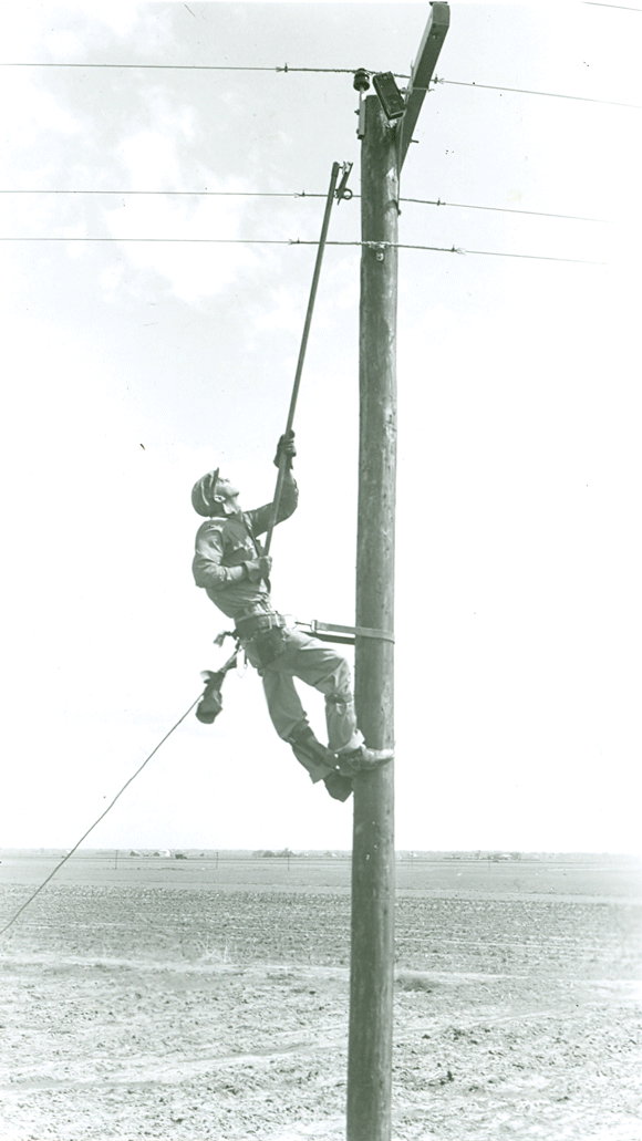 A lineman carefully reaches up to hang a fuse. From Dawson PPD's archives.