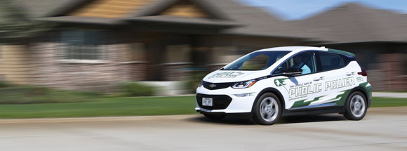 Chevy Bolt electric vehicle driving down the street. Electric vehicles are eco-friendly with low emissions and keep money in the pockets of Nebraskans. Courtesy NPPD.