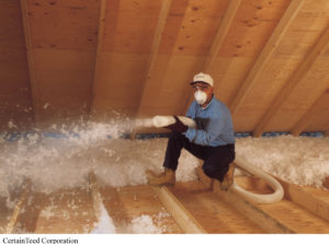 A man blows cellulose insulation into an attic