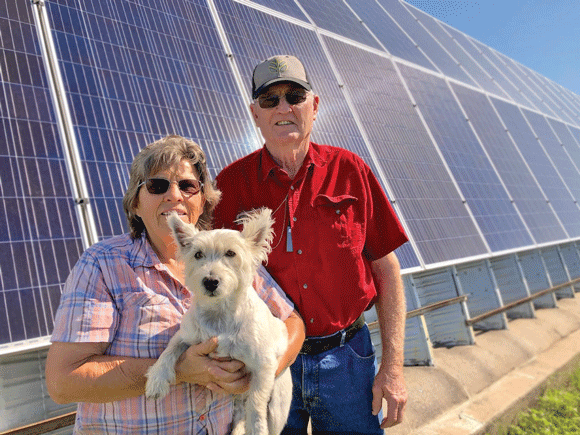 Wendell and Joanne Stevens of Kearney with their dog, Casper, stand in front of the couple's solar panel system at their home.