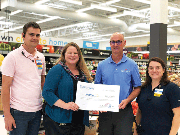 Dawson PPD Energy Services Specialist Bobby Johnson (second from right), presents Walmart employees with an EnergyWise rebate certificate. Pictured from left: Bryan Schwarz, Assistant Manager of Online Grocery, Shawna Knott, General Manager, and Maci Haney, Assistant Manager of Apparel and Home.
