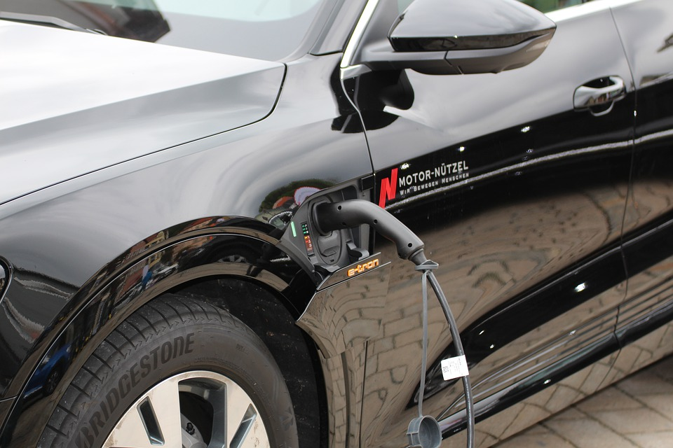 A black electric car is charged by an electric plug.